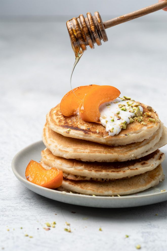 An image of a stack of pancakes with peaches and honey being drizzled on top as an example of a straight on camera angle.