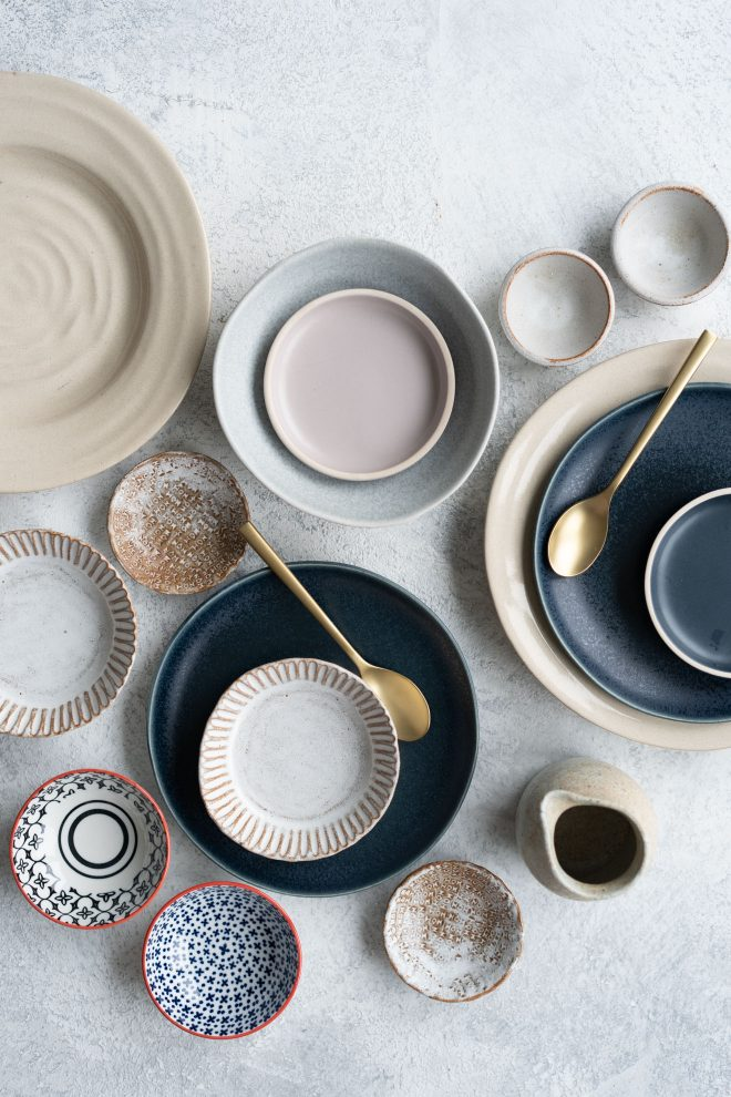 Image of handmade and hand-painted plates, cups, and bowls on a white counter space. photograph by Lauren Caris Short of Food Photography Academy