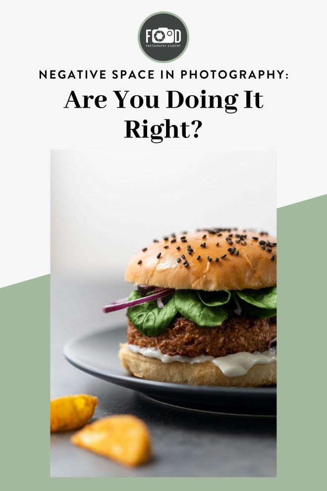 """Close up shot of a cheeseburger set against a white-gray background. Text on mage reads """"Negative Space in Photography: Are you doing it right?"""" Photograph by Lauren Caris Short of Food Photography Academy."""