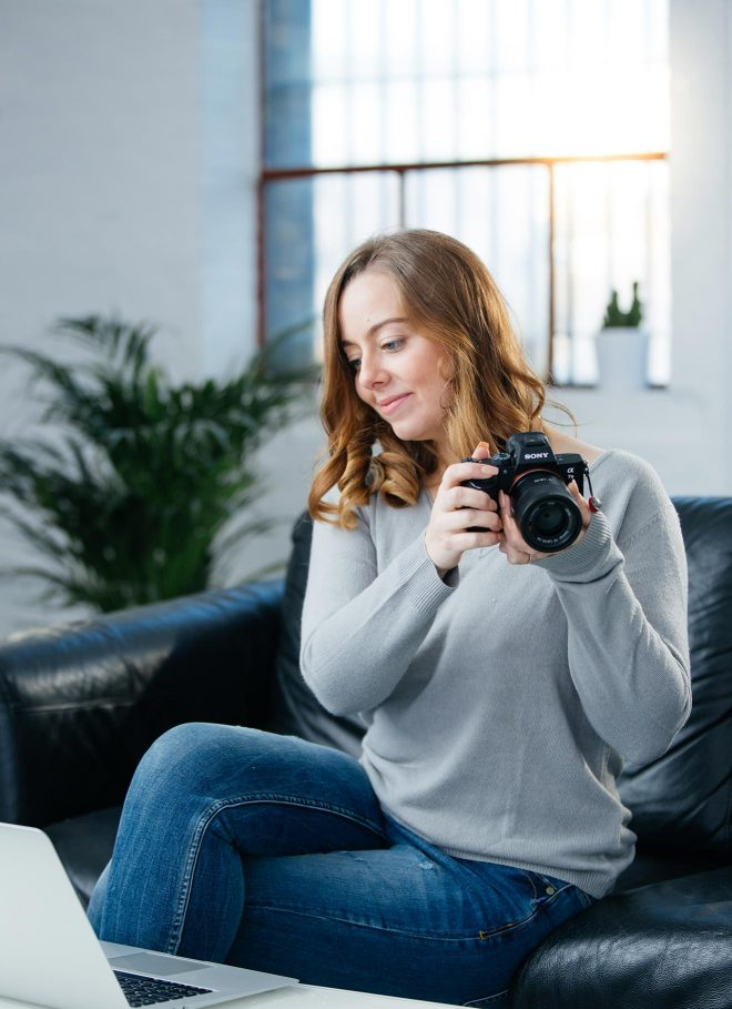 Professional food photographer, Lauren Short, sitting on a sofa holding her camera and looking at her laptop during the photo editing process.