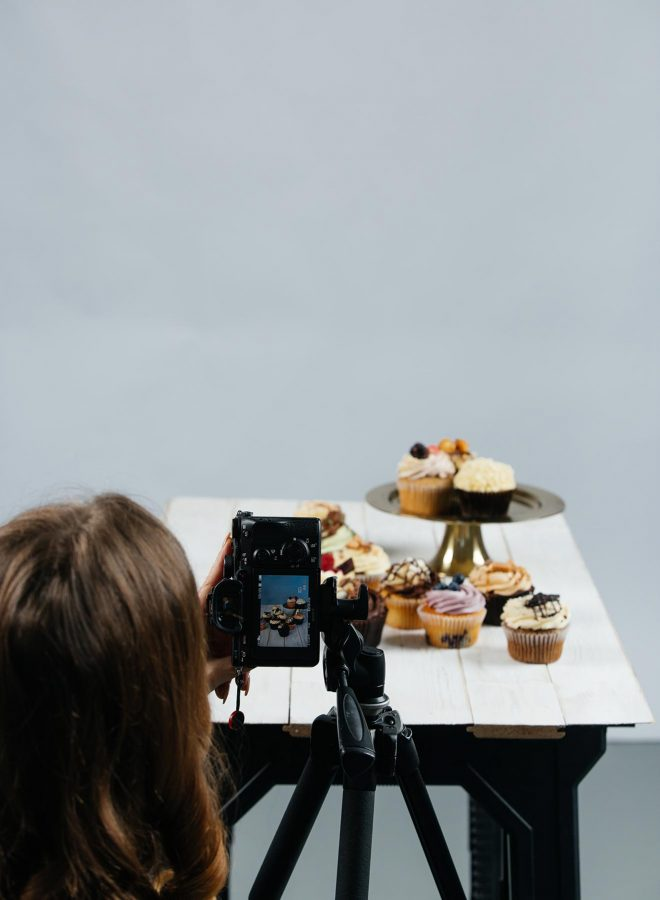 Lauren Short, a professional food photographer and educator, stands behind her camera tripod as she photographs some cupcakes a table.