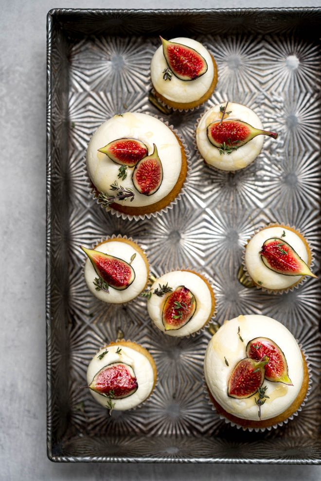 Cupcakes with icing and fig slices on top. The cupcakes are in a textured, rectangular tin. Photograph by Lauren Caris Short of Food Photography Academy.