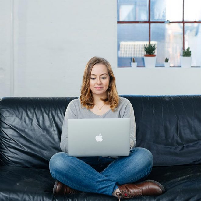 a woman sits on a couch with her legs folded and her laptop in her lap