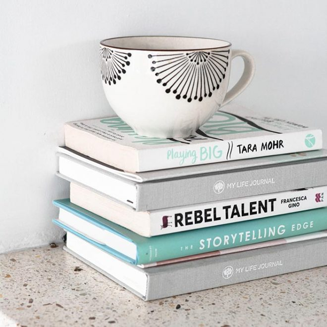 a stack of food photography books sit on a counter top with a coffee cup on top of them