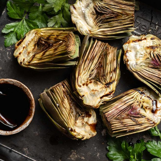 several grilled artichokes lie on a surface