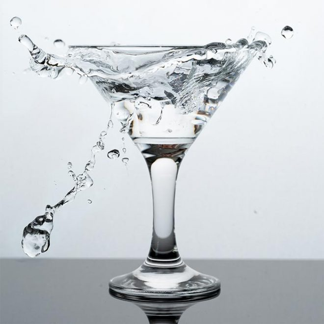 a martinie glass filled with a clear liquid splashes onto the countertop