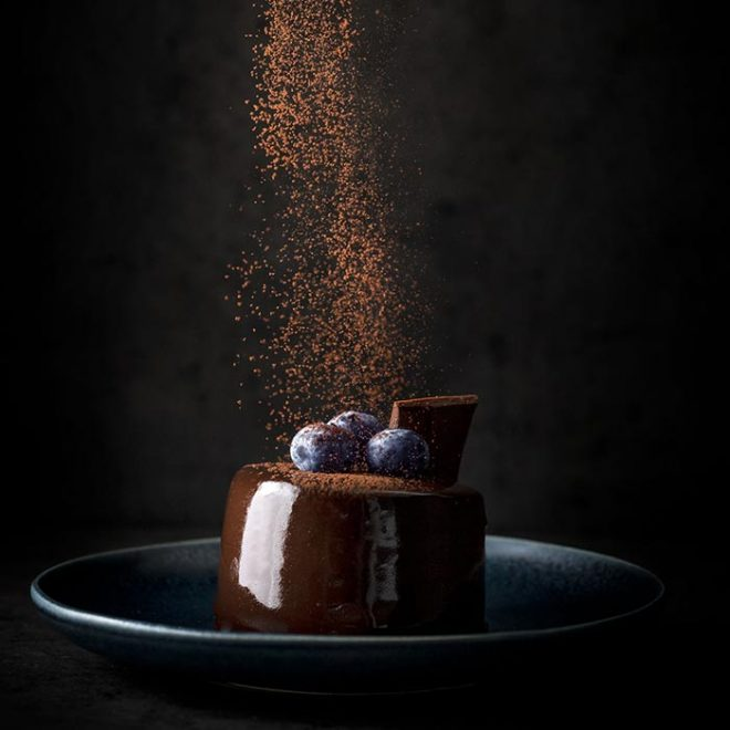 a chocolate dessert sits on a plate while chocolate powder is being sprinkled on it