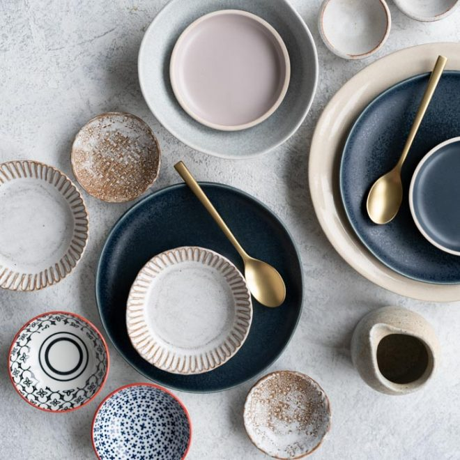 an assortment of places and bowls sit on a countertop