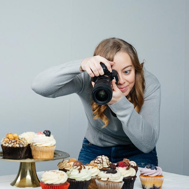 Lauren Caris Short hold her camera to her eye as she takes a picture of food