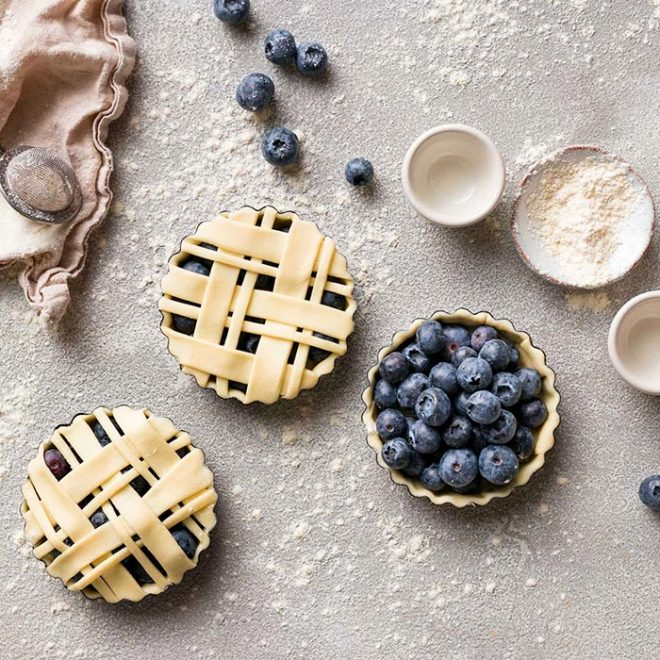 several blue berry pies are displayed while other ingredients are strone about