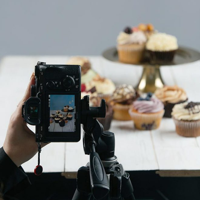 a photographer holds up their camera so you can see the display screen while a table in the background has various food items displayed on it