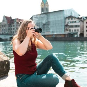 Lauren Caris Short sits near a river in the city with her camera to her eye