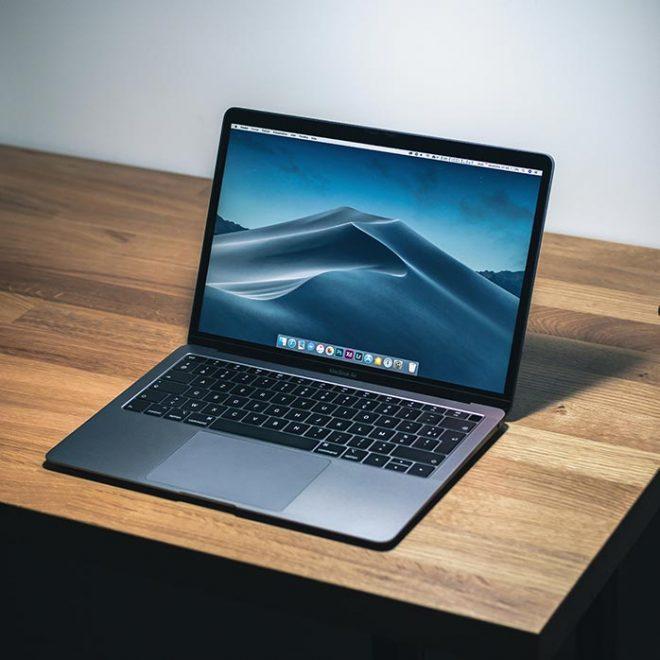 a laptop sits open on a wooden desk