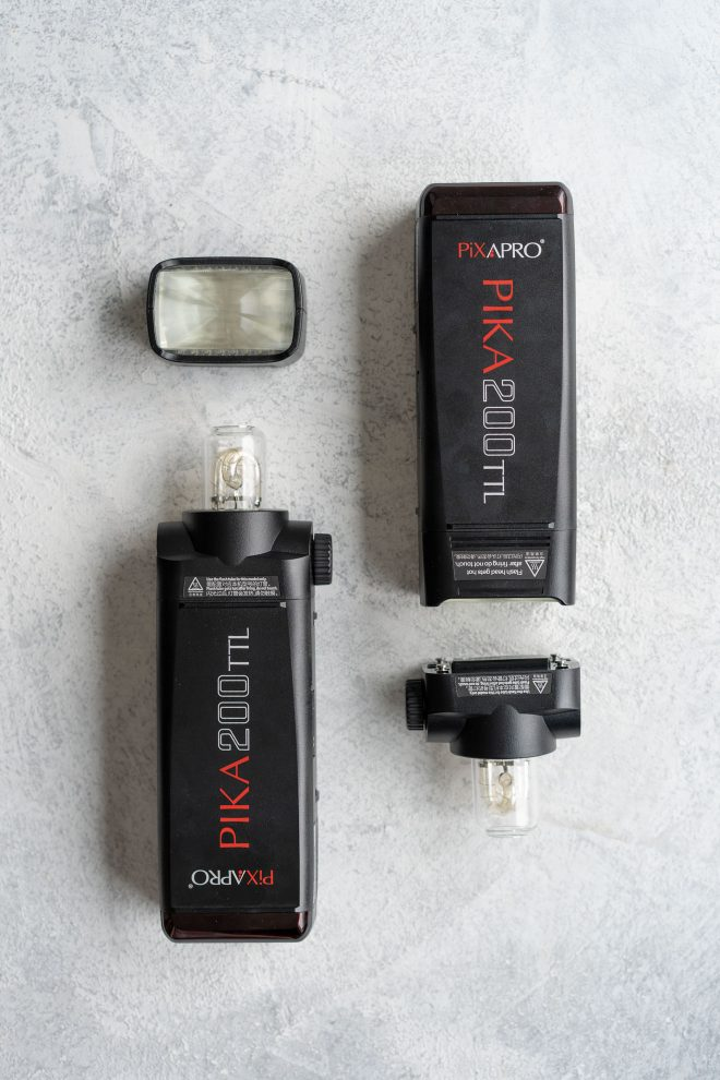 Two Pika 200 TTL flash lights on a white background as a part of essential lighting equipment for a home studio, photograph by Lauren Caris Short of Food Photography Academy