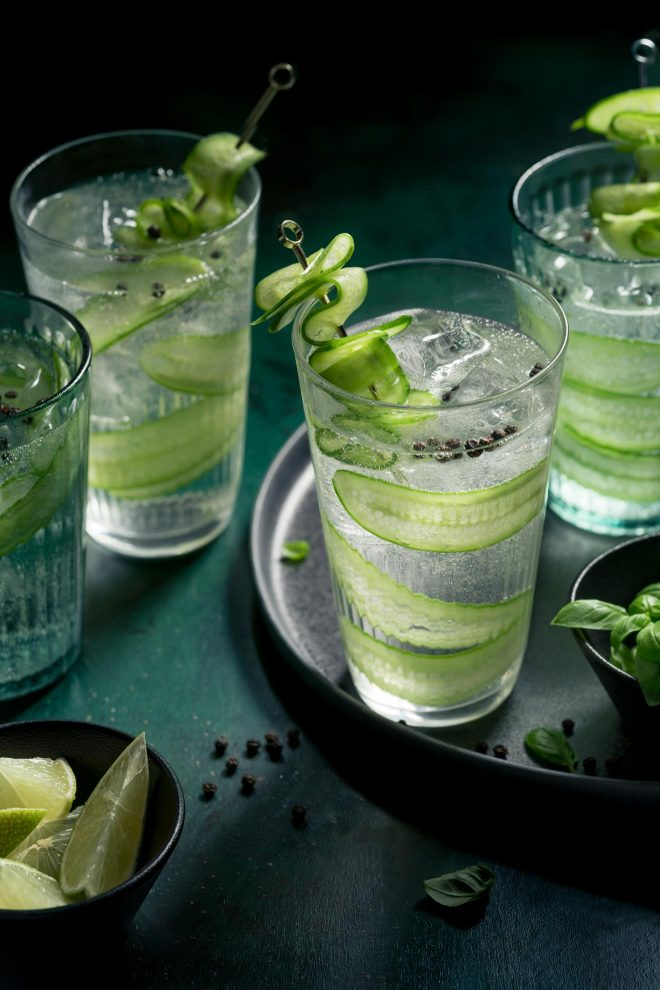 Glasses of gin and tonic with cucumber slices rest on a black tray